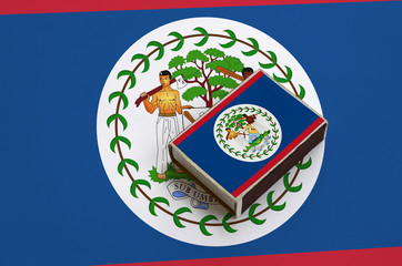 Belize flag  is pictured on a matchbox that lies on a large flag
