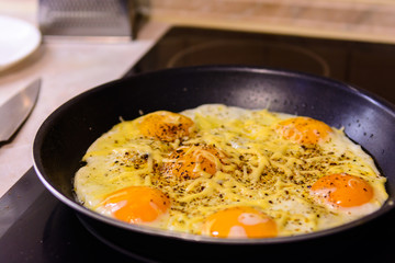 Fried eggs in the frying pan with cheese at home.