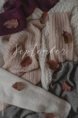 a0702b7940 Background with warm sweaters and the inscription SEPTEMBER. Pile of knitted  clothes with autumn leaves