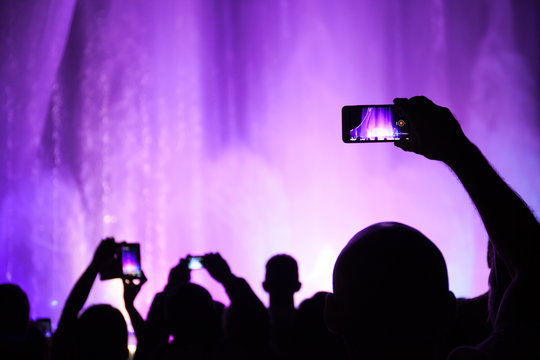 People shoot photos or video of a concert or lighting show on smartphones.