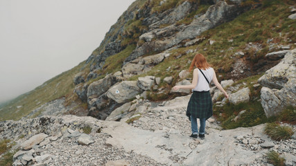 A young woman hiker walks in the mountains with photo camera. Transfagarasan, Carpathian mountains in Romania