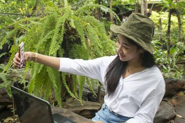Happy young asian woman taking selfie in green garden
