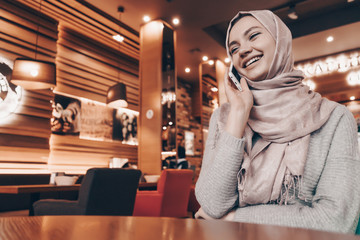beautiful smiling Arab girl in hijab sits in restaurant and talking on the phone
