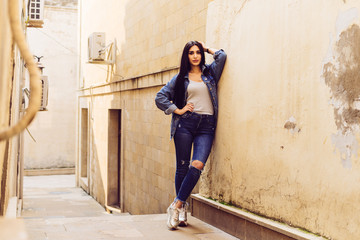 beautiful dark-haired girl in stylish clothes posing on the streets of the ancient city of Baku