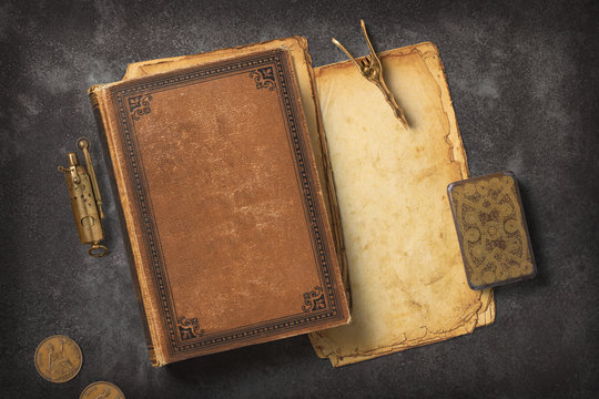 Steampunk / Gaslight themed mockup with a vintage book, a stack of grungy paper and antique brass items on a dark metal background