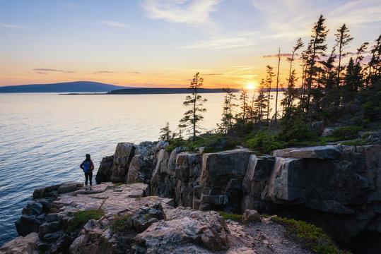 Hiker watching the setting sun at Acadia National Park