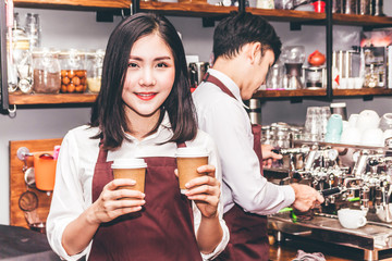 Portrait of woman small business owner smiling and holding coffee behind the counter bar in a cafe.Couple barista using coffee machine at cafe