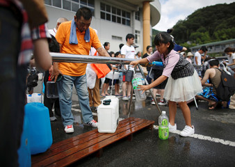 Local residents receive emergency water supply near a flooded area at Mihara Daini junior high school, which is acting as an emergency water supplying station, in Mihara, Hiroshima Prefecture