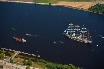 A large sailboat goes along the water area of the Daugava River. The last windjammer bark Kruzenstern.