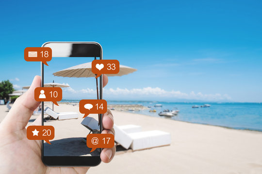 Hand mobile smart phone at the beach in summer, and social media with social network notification icons