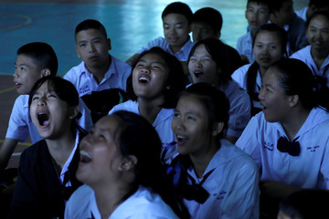Classmates laugh after a teacher announced some of the 12 schoolboys, trapped inside a flooded cave have been rescued, at Mae Sai Prasitsart school, in the northern province of Chiang Rai
