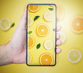 Taking Picture With Infinity Display Smartphone. Orange Leaves Citrus Pattern on Yellow Background Minimal Flat Lay