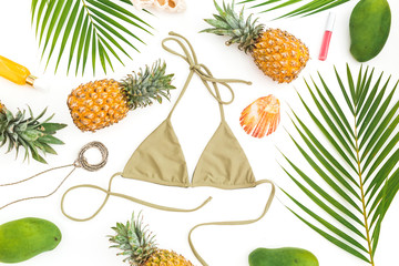 Tropical concept. Pineapple and mango fruits, palm leaves, cosmetics with bikini swimwear on white background. Flat lay, top view.