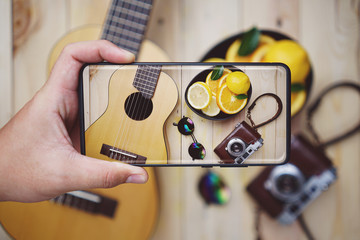 Taking Picture With Infinity Display Smartphone. Guitar, Vintage Camera, Fresh Orange Lemon In a Bowl, and Sun Glasses on Wooden Background