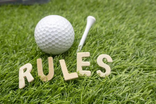 Rules of golf with golf ball and wording rules are on green grass