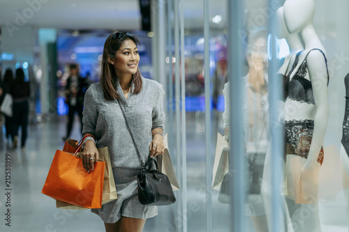 e86234ad0 Happy Asian woman holding the shopping bag and looking for new fashion  underwear in Dressmaker through glass shop store