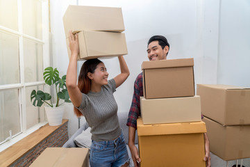 Asian young couple carrying big cardboard box for moving in new house, Moving and House Hunting concept, selective focus