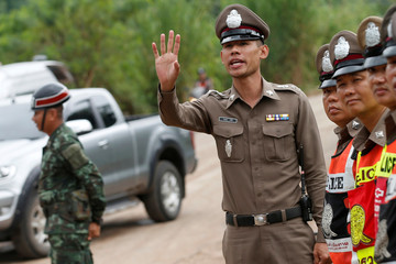 Police officers stand as they block to rod of  Tham Luang cave complex  in the northern province of Chiang Rai