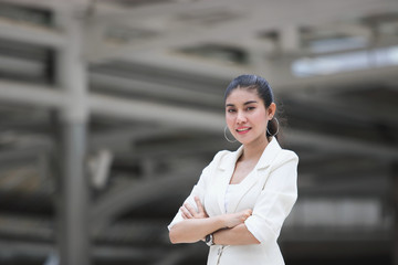 Confident young Asian business woman crossing one's arms at outdoors.
