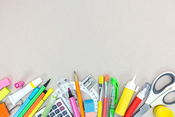 school and office stationary on grey table. flat view