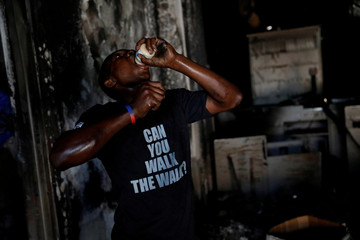 A boy eats a jar of baby food in a supermarket that was looted during protests against fuel price increases in Port-au-Prince