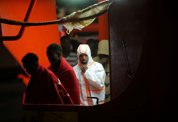 Migrants leave a rescue vessel after arriving at the port of Malaga