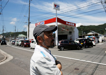 Local residents queue to refuel their vehicles at a gas station near a flooded area in Mihara