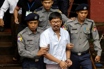 Detained Reuters journalist Wa Lone is escorted by police while leaving Insein court in Yangon