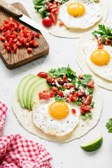 Mexican tortilla with salsa, avocado and egg on concrete background, selective focus. Tasty tacos