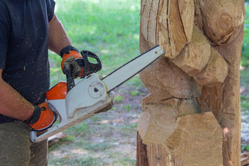 Man with a chainsaw creates a sculpture made of wood. Woodcarving