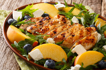 Summer diet food: grilled chicken breast with fresh peaches, blueberries, arugula and feta cheese close-up on a plate. horizontal