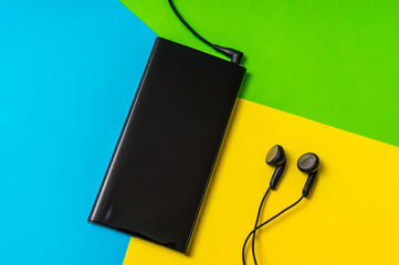 Mobile phone with headphones isolated on colorful background
