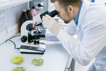 Side view portrait of young scientist looking in microscope while doing research in medical laboratory
