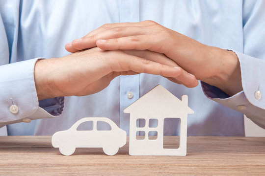 Insurance for the car and the house. Man in shirt covers his hands with his house and car