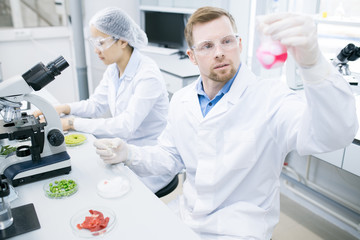 Portrait of two scientists doing research studying food substances in laboratory, focus on modern young man holding beaker