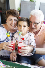 Grandparents and grandson drinking watermelon juice on the terrace in summer