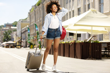 Love travelling. Upbeat curly woman carrying a suitcase and smiling happily, having just arrived at a new city