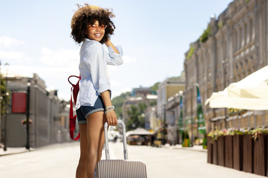 Love journeys. Joyful female tourist smiling at the camera while standing half-turned and holding a little suitcase
