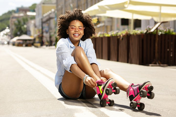 Roller-skating lover. Pleasant curly girl smiling at the camera and putting on roller skates while sitting on the asphalt in the street