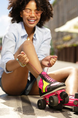 Enjoy roller-skating. Pleasant curly girl tying roller skate laces and smiling cheerfully while sitting on the asphalt