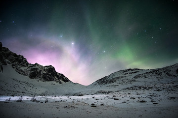 Aurora borealis with sunrise shining over mountain range in the night sky