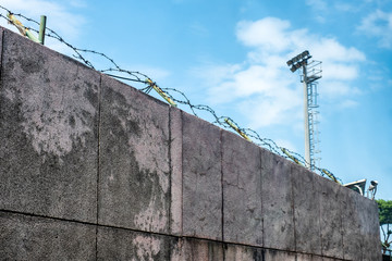 Wall stone with coils barbed wire and security camera