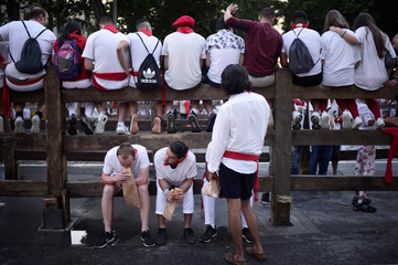 Revellers eat baguettes before the bull run on the fourth day of the San Fermin festival in Pamplona