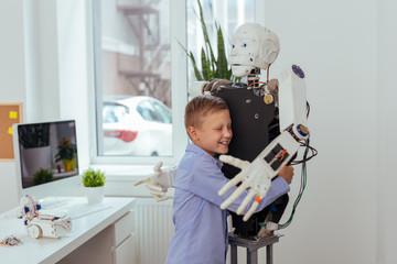 Best friend. Joyful happy boy smiling while hugging a robot