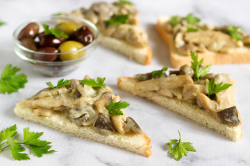 Triangular sandwiches with summer mushrooms cooked with cream and herbs served with olives.
