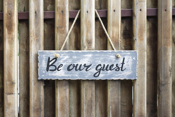 Photo of wooden table with lettering 'Be our guest' on the wooden background