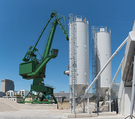 Exterior view of a cement factory with crane and concrete mixing silo