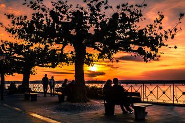 Senioren Silhouetten an Uferpromenade bei Sonnenuntergang
