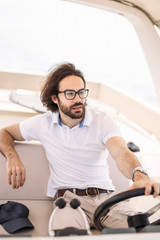 Young handsome bearded yachtsman driving his motor boat hurrying to pick up his friends from pier