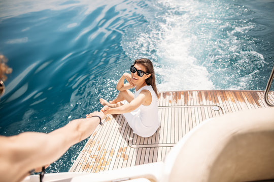 Young happy woman wearing sunglasses and stylish stripped overall, posing against beautiful blue sea water, having vacations on exotic beach, posing for travel magazine. Summer and leisure concept